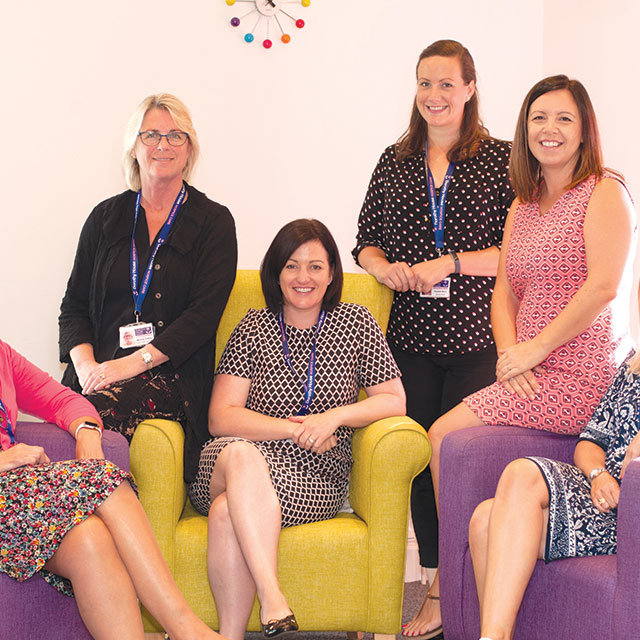A group of six nurses standing sitting together chatting